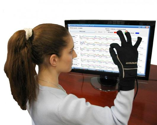 Woman using a connected glove to translate sign language into written and auditory language